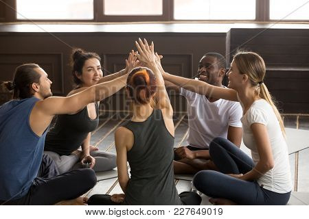 Diverse Happy Yogi People Reach Hands To Give High Five Sitting On Mats At Yoga Seminar Training, Mu