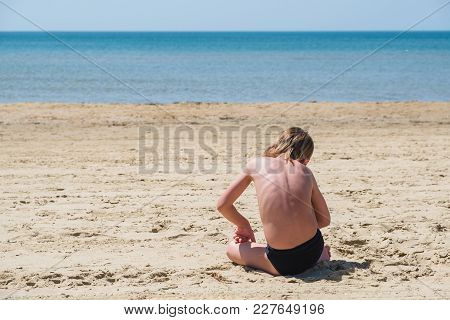 Blond Baby Wearing A Blue Pants Sitting On The Beach, Waitting For Someone From The Sea.