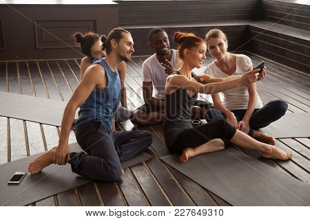 Smiling Young Multiracial People Making Selfie On Smartphone Before Yoga Training Sitting On Mats In