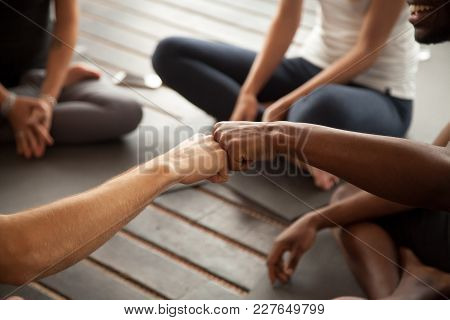 African And Caucasian Men Fist Bumping At Group Meeting In Gym Studio, Two Multiracial Black And Whi