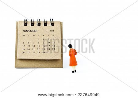 November. Two Thousand Eighteen Year Calendar And Miniature Plastic Woman On White Background.