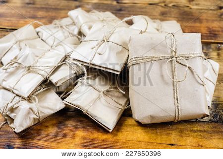Close-up Many Gifts Wrapped Kraft Paper On Wooden Background. One Big Present
