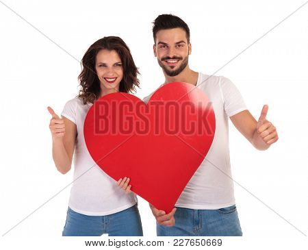 happy in love couple holding heart and make ok sign on white background