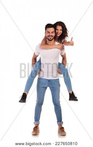 woman making ok sign while she rides on the back of her man on white background