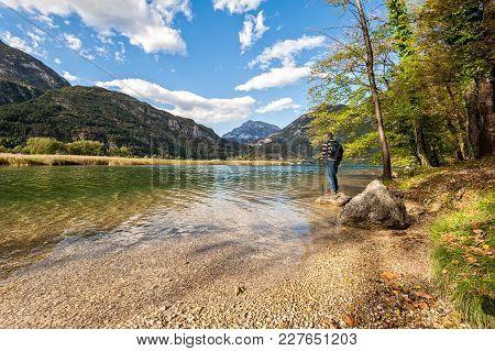 Hiker Standing On The Lake Among The Mountains