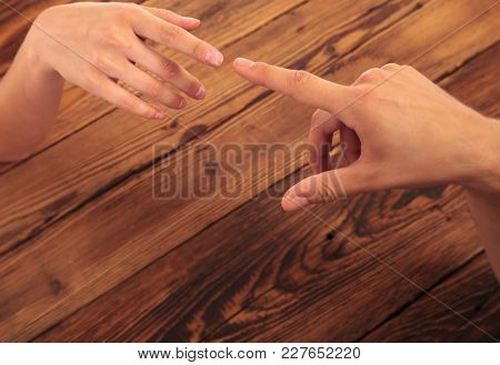 man and woman touching fingers on a wooden background