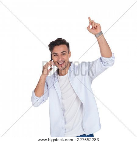 smiling excited man talking on the phone and points up while celebrating good news on white background