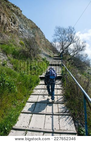 Unrecognizable Boy Of 6-years Rises To The Top Of The Mountain On The Bridge Along The Slope. Vertic