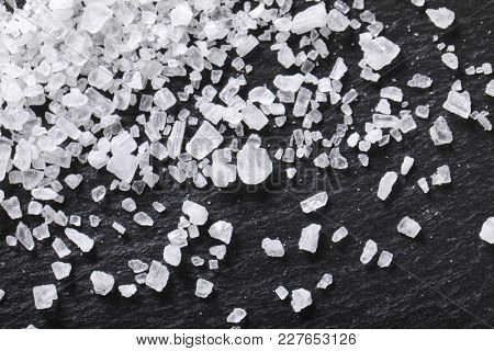 crystals of coarse grained sea salt on black background - close up
