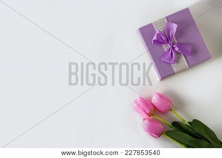 Three Pink Tulips And A Gift Box On The White Background. Artificial Flowers. Copy Space. Flat Lay,