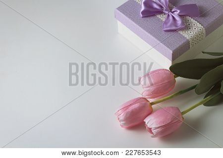 Three Tulips And A Gift Box On The White Background. Artificial Flowers. Copy Space