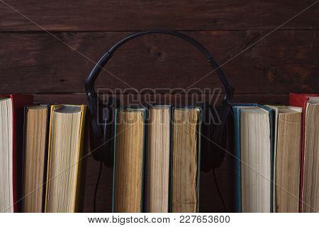 Headphones Put On Folded Books On The Dark Wood Background
