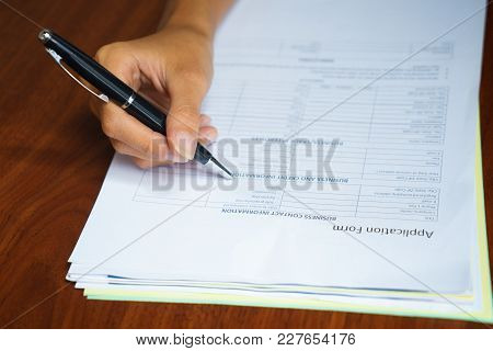 Close-up Of Hand Of Female Candidate Filling In Application Form At Table. Job Interview Concept
