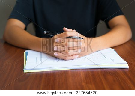 Close-up Of Hands Clasped On Papers Of Businesswoman Sitting At Table And Holding Pen. Meeting And J