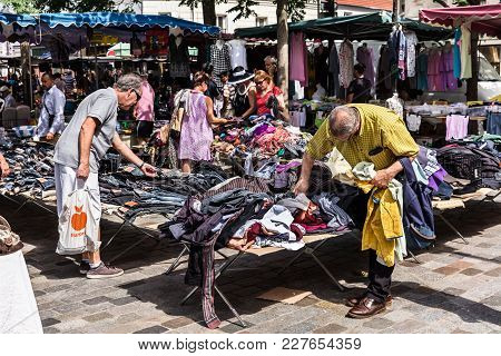 Men Choose Clothes At The Flea Aligre Market. Paris, France