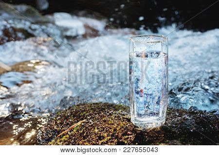 A Transparent Glass Glass With Drinking Mountain Water Stands In The Moss Stone On Sun Beame Against