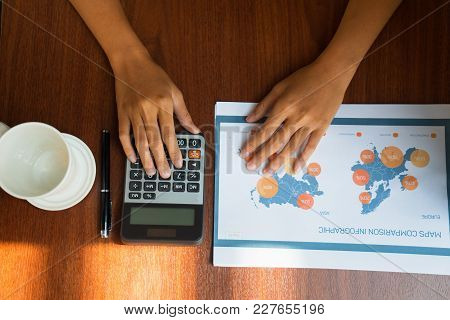 Top View Of Hands Of Female Analyst Sitting At Table And Working With Documents And Calculator. Acco