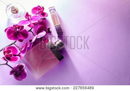 Bottles Of Perfume With Violet Orchid On Purple Background