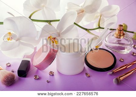 Set Of Natural Cosmetics And Make-up Brushes With White Orchid On Pink Background