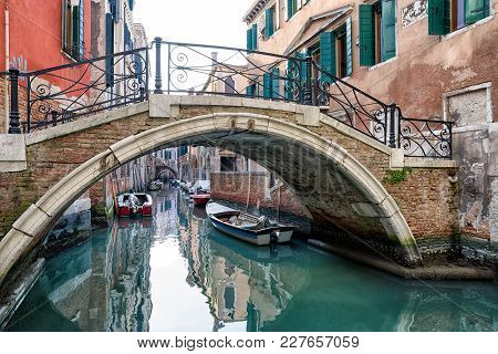 Venice, Italy - February 11: Footbridge And Boats In Water Canal On February 11, 2018 In Venice