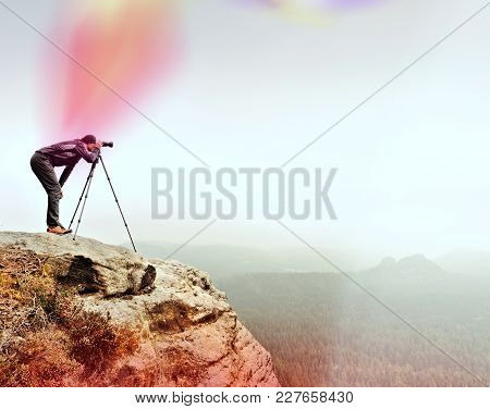 Hiker With Camera On Tripod Takes Picture From Rocky Summit. Alone Photographer At Edge Photograph M
