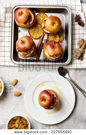Red Baked Apples With Granola, Cinnamon, Nuts And Honey On Stone Background. Healthy Vegetarian Dess