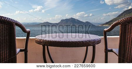Empty Of Brown Rattan Chairs On Balcony Hotel Room With Mountain And Ocean View At Summer Day