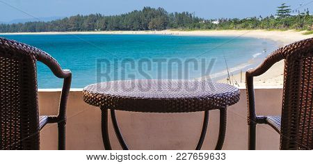 Empty Of Brown Rattan Chairs On Balcony Hotel Room With Sand Beach And Blue Ocean