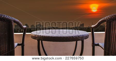 Empty Of Brown Rattan Chairs On Balcony Hotel Room At Sunset In The City