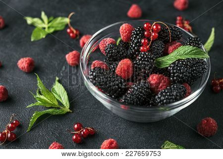 Glass Plate With Ripe Red Blackberries, Raspberries, Currant And Green Mint Leaves On A Black Surfac