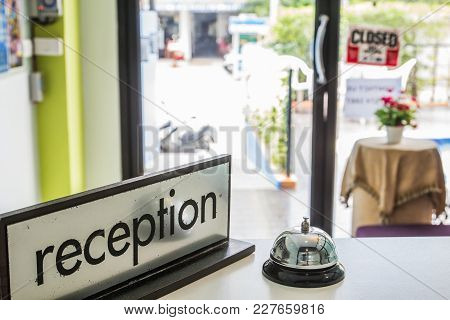 Silver Bell And Reception Sign On White Counter Bar In Lobby Hotel