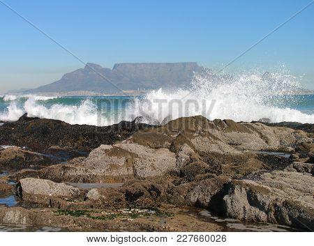 From Cape Town, South Africa, Waves Smashing Over Some Rocks In The Fore Ground, With Table Mountain
