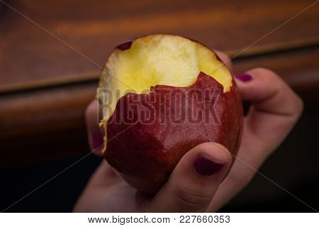 Someone Holding A Bitten Apple In Their Hand
