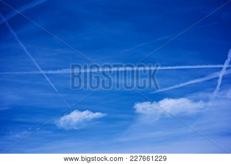 Dark Blue Sky With Vapor Trails And Light Clouds In Sunny Day Outdoors