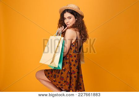 Photo of amazing young woman standing isolated over yellow background. Looking camera holding shopping bags.