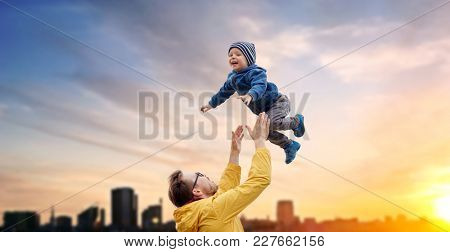 family, childhood and fatherhood concept - happy father and little son playing and having fun outdoors over evening tallinn city background
