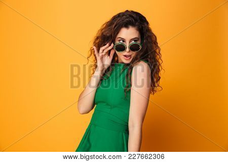 Image of beautiful young woman standing isolated over yellow background. Looking aside wearing sunglasses.