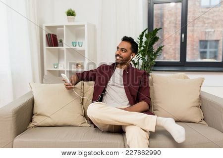 technology, leisure and people concept - happy man in earphones with smartphone listening to music at home