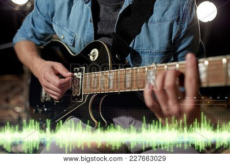 music, people and recording studio concept - close up of male guitarist playing electric guitar and sound frequency diagram