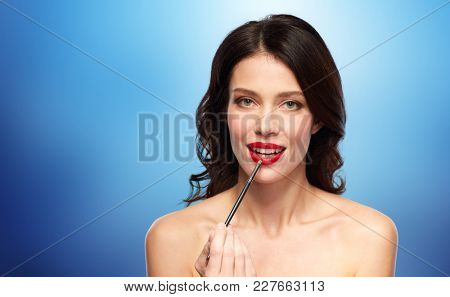 beauty, cosmetics and people concept - beautiful young woman with make up brush applying red lipstick over blue background