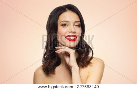 beauty, make up and people concept - happy smiling young woman with red lipstick posing over beige background