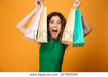 Image of excited surprised young woman standing isolated over yellow background. Looking camera holding shopping bags.