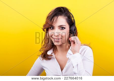 Customer Support Worker With A Headphone Set On Her Head On Yellow Background