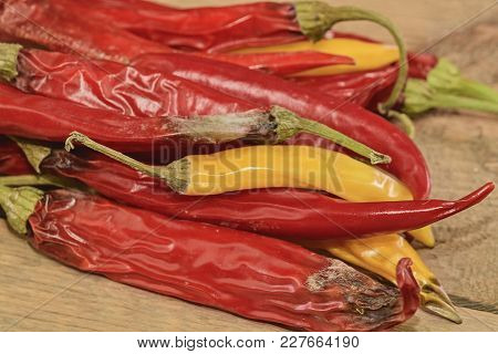 Shrinking And Mould Chili Peppers On Wooden Background. Rotten Chili Peppers. Flat Design.