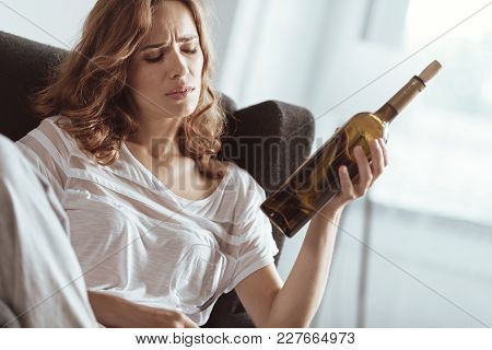 The Best Medication For Me. Low Angle Shot Of An Emotionally Exhausted Lady Holding A Bottle Of Wine