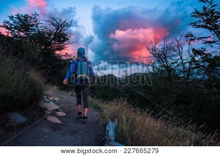 Hiker walks on the mountain trail during bright and colorful sunrise
