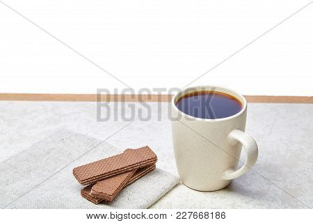 White Ceramic Porcelain Coffeecup With Stack Of Waffles On White Cotton Napkin On Light Concrete Bac