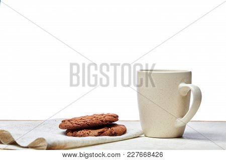 White Ceramic Porcelain Coffeecup With Stack Of Chocolate Chip Cookies On White Cotton Napkin On Lig