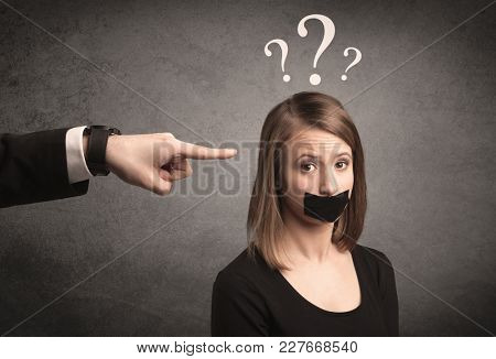 Caucasian business hand pointing at female employee with big white question mark above her head