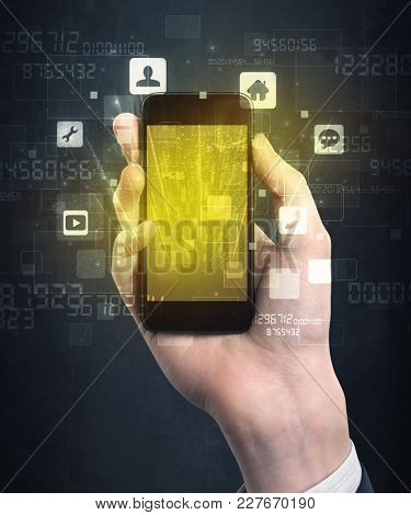 Caucasian hand in business suit holding a smartphone with golden-yellow holographic screen